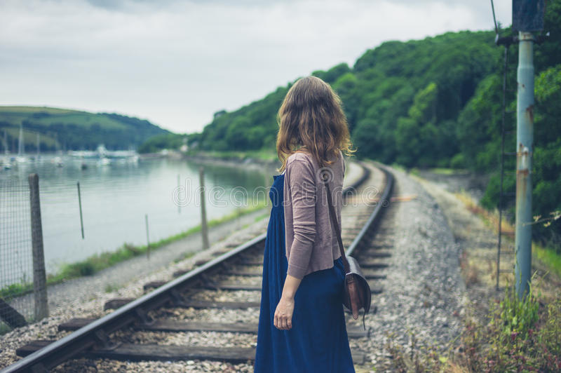 Woman walking by railroad tracks and river. A young woman is walking near the railroad tracks by a river royalty free stock images