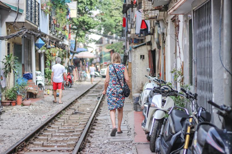 A woman is walking on the railway in Train street, Hanoi, Vietnam royalty free stock image