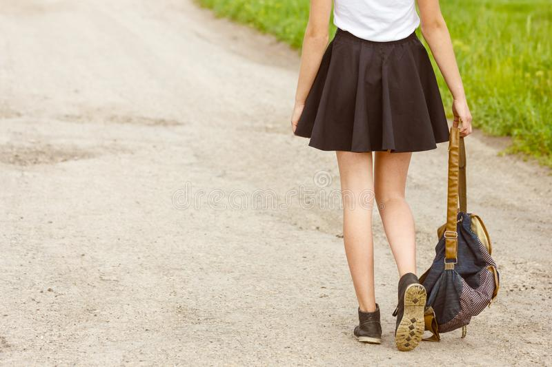 Woman walking on the road holding backpack in hand, travel concept, hitchhiking royalty free stock photography