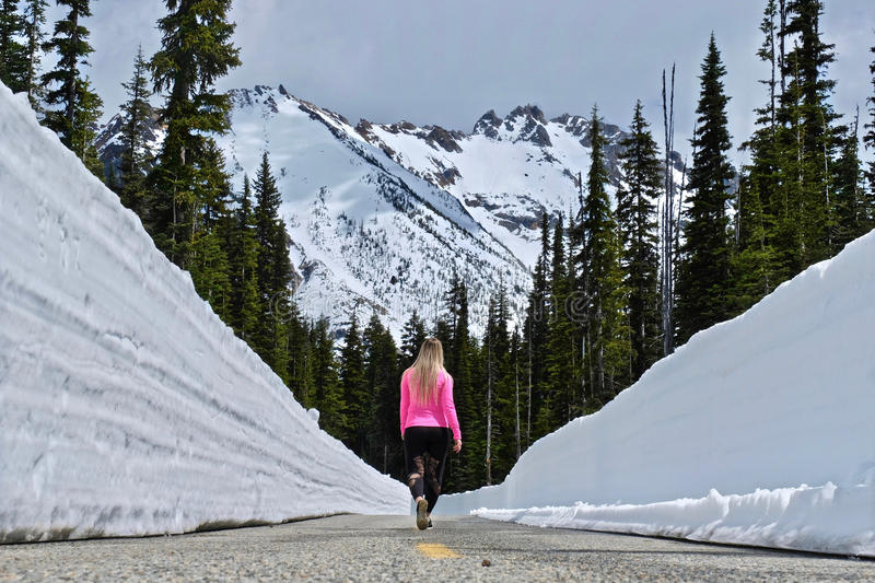 North Cascades Mountains with snow and woman walking on the road with snow walls. North Cascades National Park. Bellingham. Seattle. Cascade mountains stock images