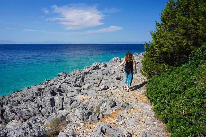 Woman walking on rocky beach stock photos
