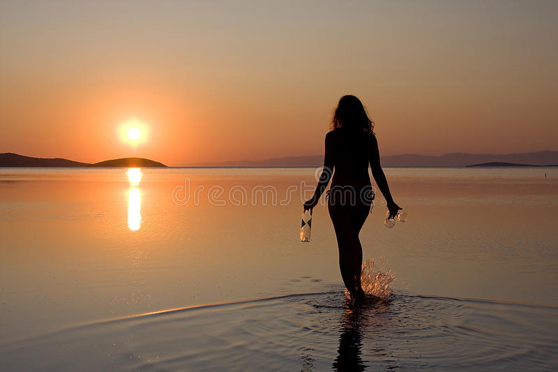 Woman walking in sea at sunset royalty free stock images