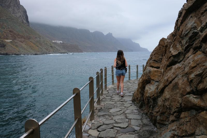 Woman walking on the seafront with mountains and cloudy sky on background stock images