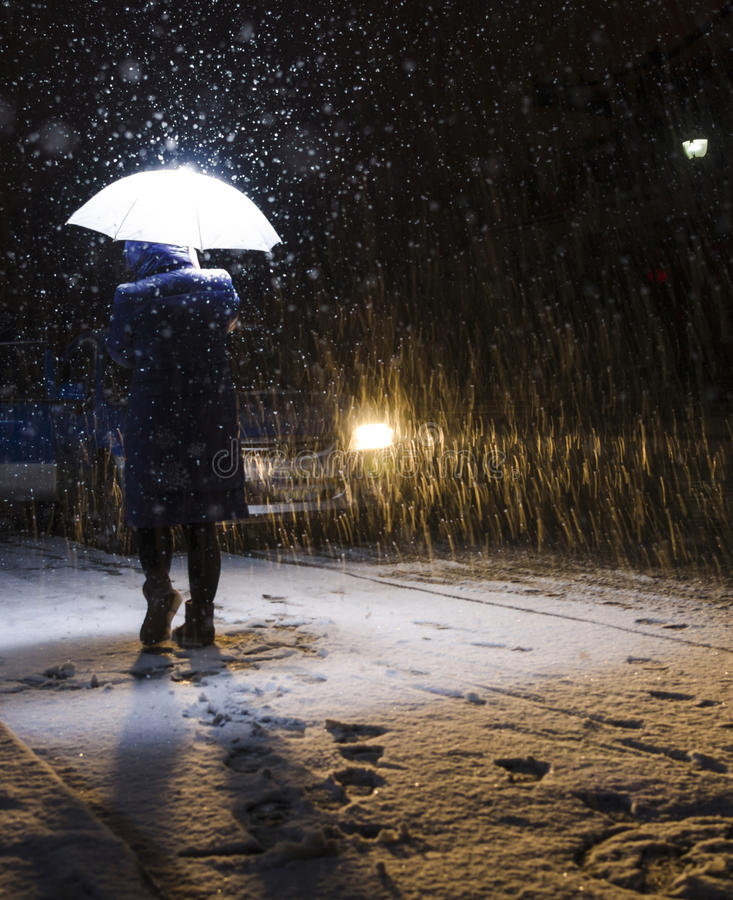 Woman walking in the snow. In a snowy evening, a woman through a curb royalty free stock image