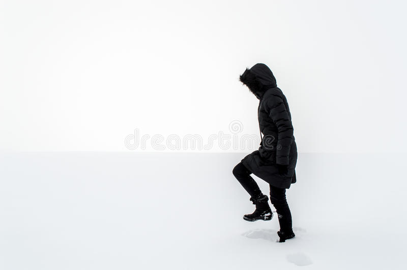 Woman walking in a snowy field. Woman in black walking in a snowy field stock photo
