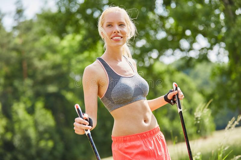 Woman with walking sticks. Nordic walking in the nature stock photography