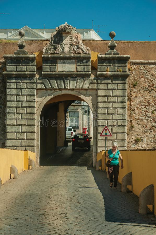 Woman walking a street going toward a city wall gateway stock image