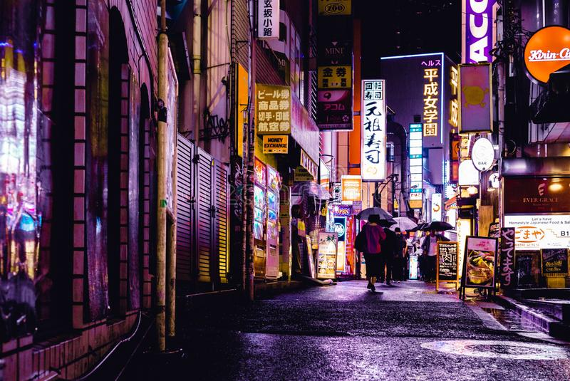 Woman Walking in the Street during Night Time stock images