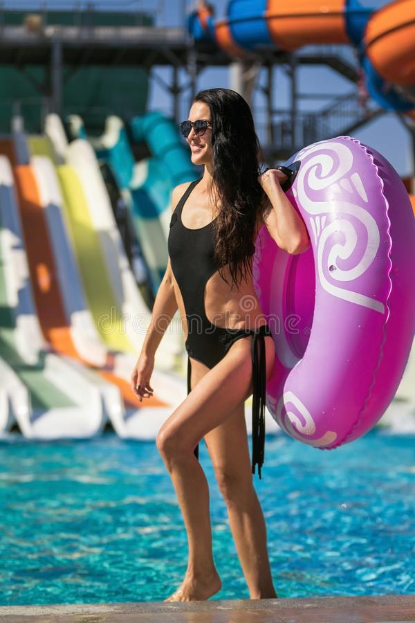 Woman walking with swim ring near pool and slides. Beautiful smiling woman with slim figure in black swimwear holding a swim ring walking near the swimming pool stock images