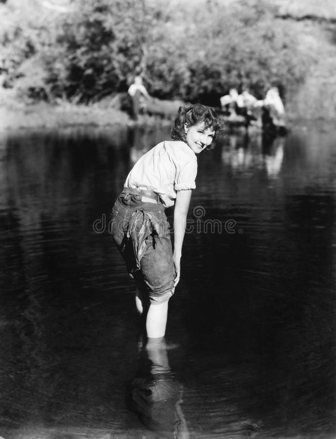 Woman walking though the water with her pants rolled up royalty free stock image