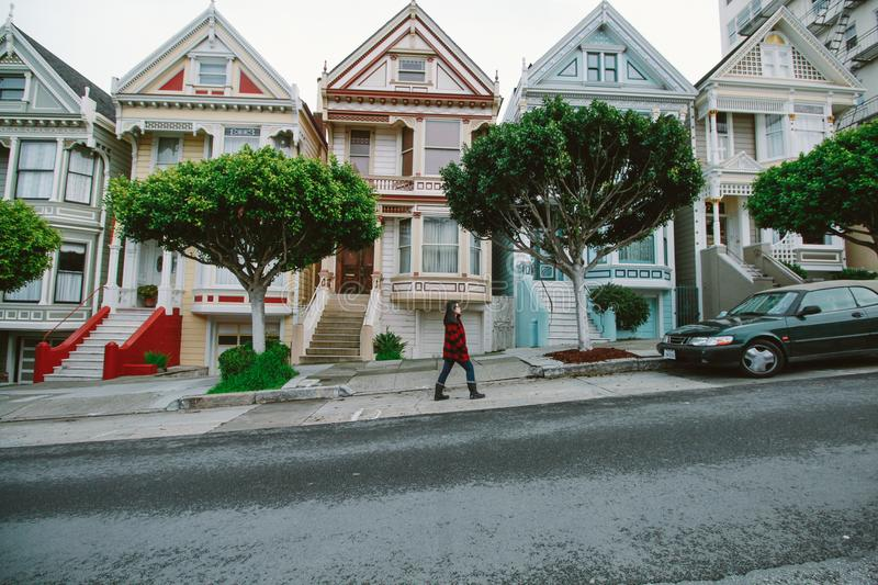 Woman Walking Toward Black Sedan Parked In Front of Colorful Houses stock image