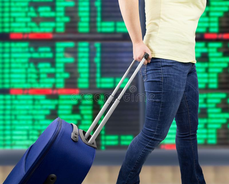 My travel begins. Woman walking travel bag at international airport with the flight information board background stock photography