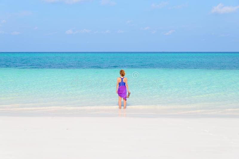 Woman walking on tropical beach. Rear view white sand beach turquoise trasparent water caribbean sea real people. Indonesia Kei royalty free stock photos