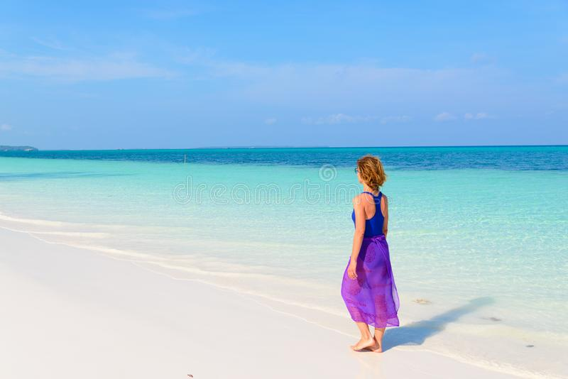 Woman walking on tropical beach. Rear view white sand beach turquoise trasparent water caribbean sea real people. Indonesia Kei stock photography