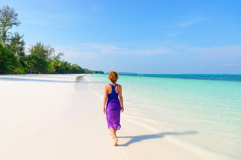 Woman walking on tropical beach. Rear view white sand beach turquoise trasparent water caribbean sea real people. Indonesia Kei stock images