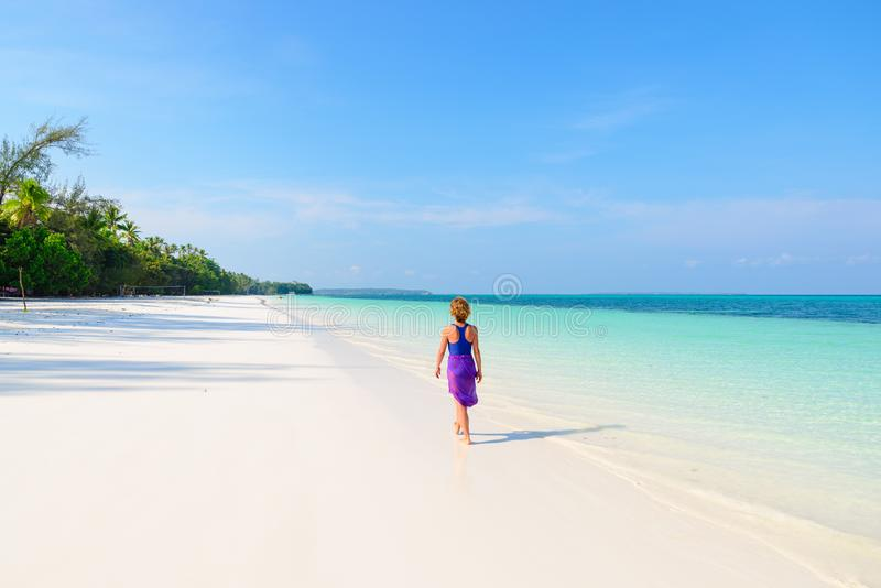Woman walking on tropical beach. Rear view white sand beach turquoise trasparent water caribbean sea real people. Indonesia Kei royalty free stock images