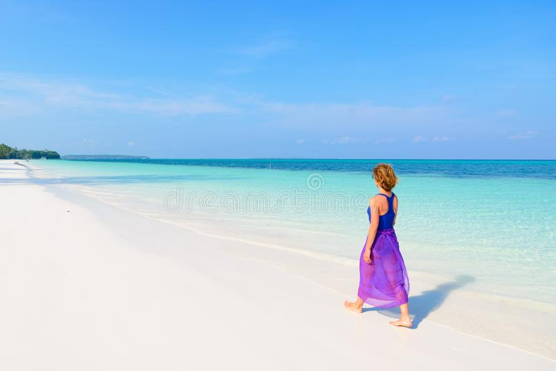 Woman walking on tropical beach. Rear view white sand beach turquoise trasparent water caribbean sea real people. Indonesia Kei stock image
