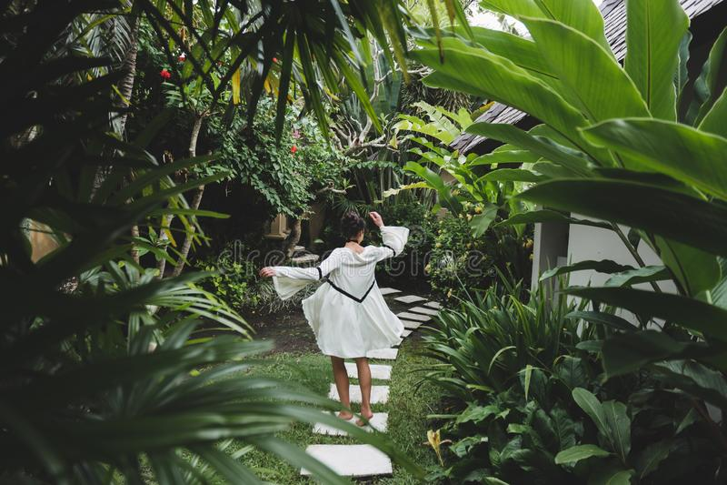 Woman walking in tropical garden in Bali Ubud in white dress. Woman walking in tropical garden in white dress. Brunette with long black hair. Fashion tunic royalty free stock image