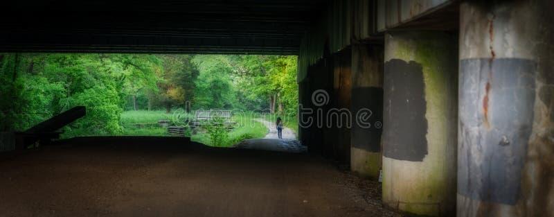 Woman walking under highway bridge along Chesapeake and Ohio Canal stock photography