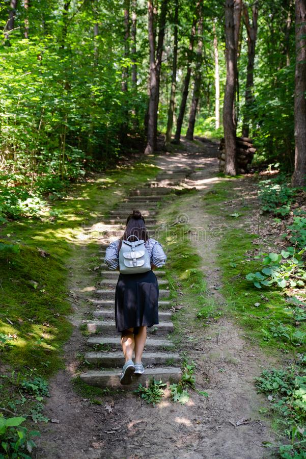 woman walking up by old stairs in forest stock image