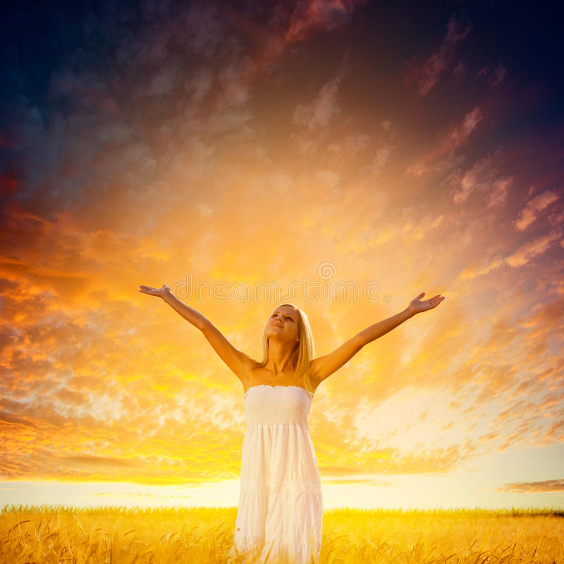 Woman walking on wheat field over sunset royalty free stock image