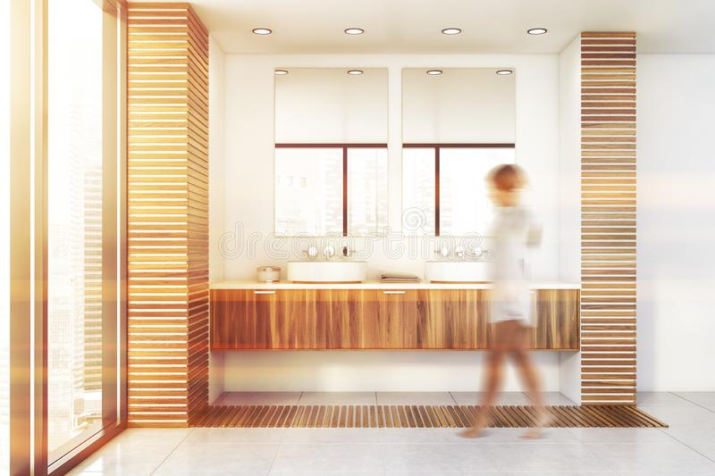 Woman walking in white bathroom with double sink. Blurry young woman walking in modern bathroom with white and wooden walls, tiled floor, double sink and two royalty free stock photography