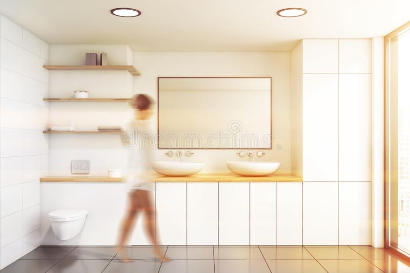 Woman walking in white bathroom with toilet. Young woman walking in luxury bathroom with white walls, tiled floor double sink with rectangular mirror and toilet stock image