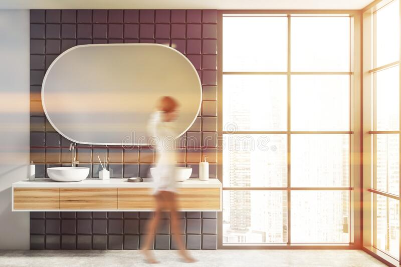 Woman walking in white and gray bathroom with sink stock photo