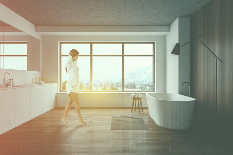 Woman walking in white and wooden bathroom. Young woman walking in modern bathroom with white and wooden walls, comfortable bathtub and double sink. Toned image royalty free stock image