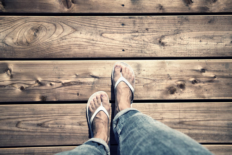 Woman walking on wooden floor. A woman walking on wooden floor, point of view perspective. A woman with white flip-flops and jeans walking alone on old wooden royalty free stock images