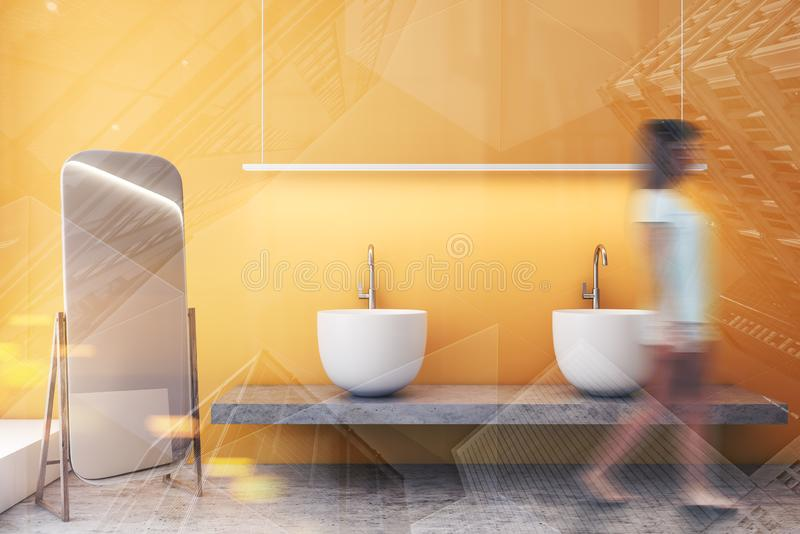 Woman walking in yellow bathroom with sink. Young woman walking in luxury bathroom interior with yellow walls, massive double sink standing on stone shelf and stock photography