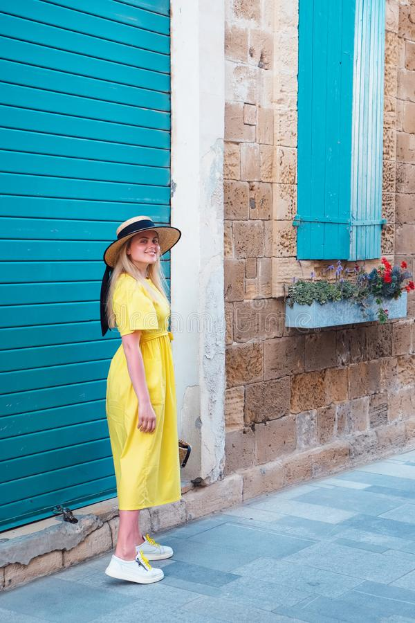 Woman walking in yellow dress at Paphos old city royalty free stock photo