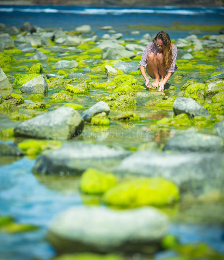 Woman Walks Alone on a Green Reef stock images