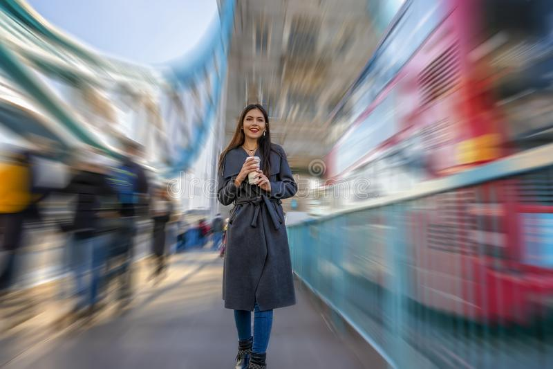 Woman walks down the Tower Bridge with a coffee in her hand. Young city urban woman walks down the Tower Bridge in London with a coffee in her hand royalty free stock image