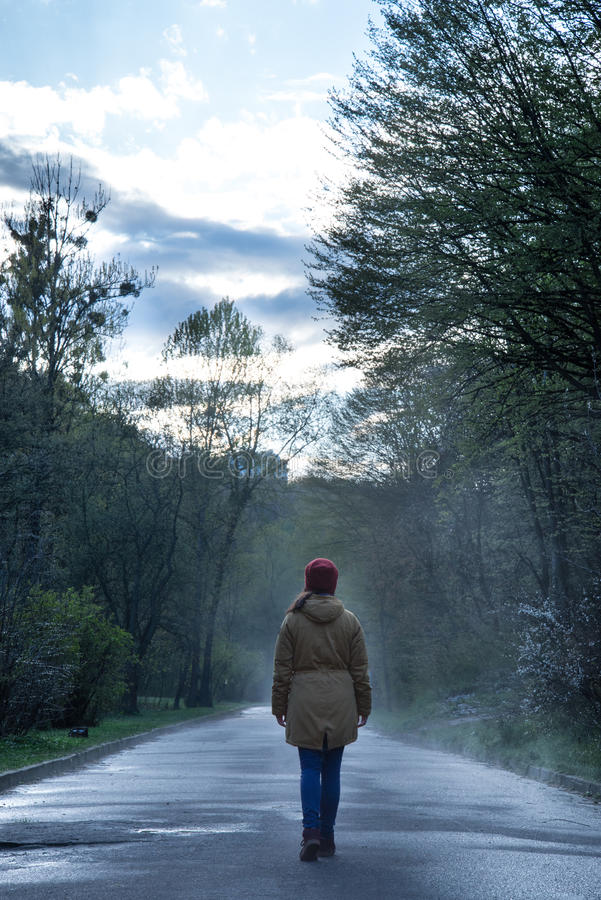 Woman walks at the park in rainy foggy day stock image