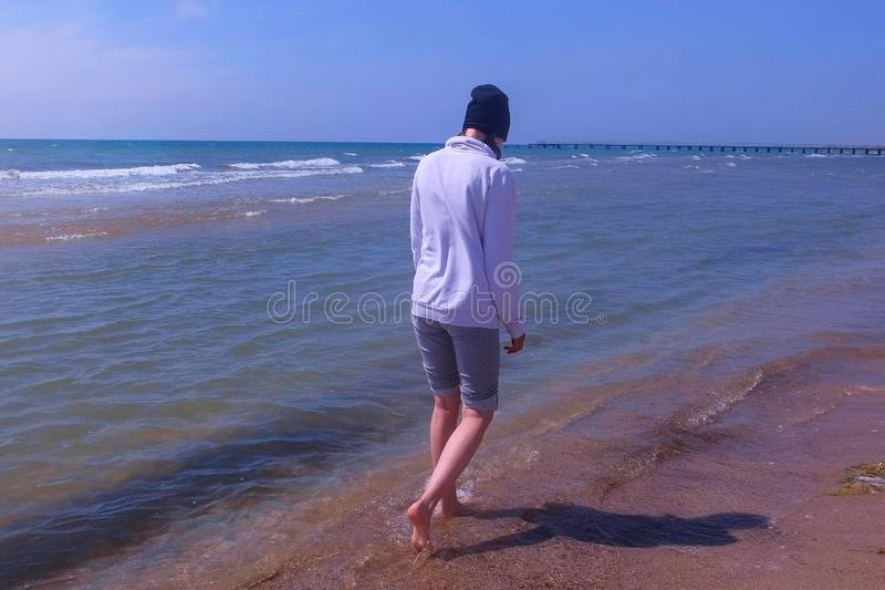 Woman walks at sea water on sandy beach off-season wears in hoodie and hat. Woman traveller walks at sea water on sandy beach off-season wears in hoodie and hat royalty free stock photo