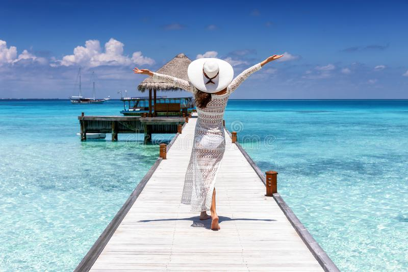 Woman walks on a wooden jetty over tropical waters of the Maldives islands royalty free stock photos