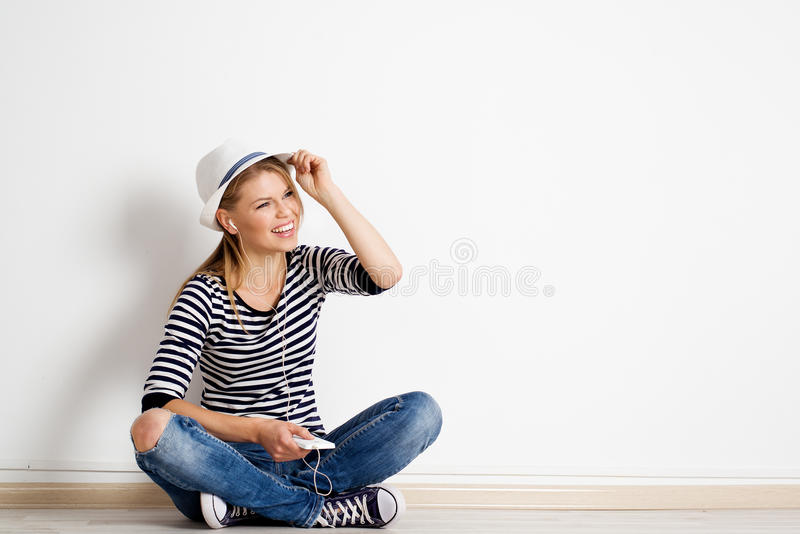 Woman at wall listening music. Stylish young female having fun and relaxing in her apartment. Cheerful Caucasian woman sitting at empty wall with her smart phone royalty free stock images