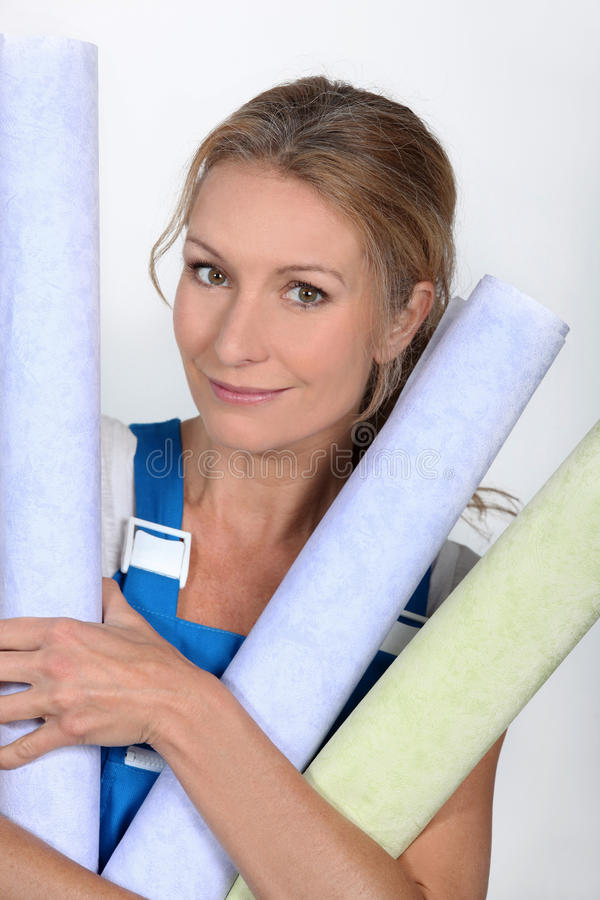 Woman with wallpaper rolls. Pretty woman with wallpaper rolls stock image