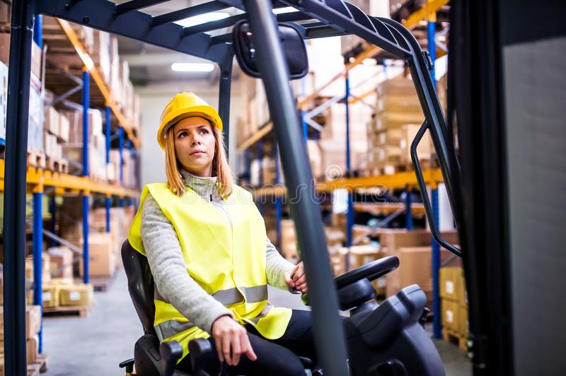 Woman warehouse worker with forklift. Beautiful young woman warehouse worker with forklift royalty free stock image