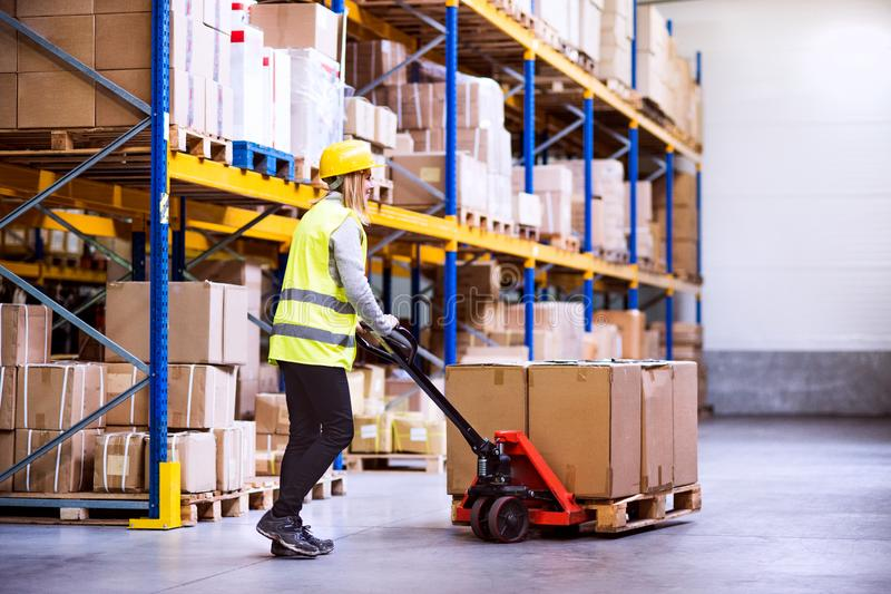 Woman warehouse worker with hand forklift truck. royalty free stock photography