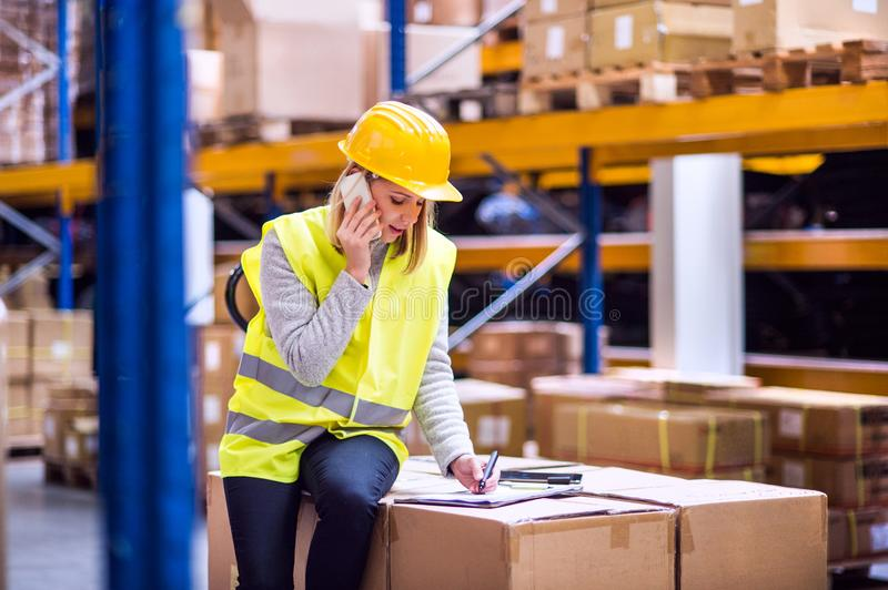 Woman warehouse worker with smartphone. stock image