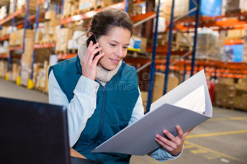 Woman warehouse worker or supervisor with smartphone stock photo