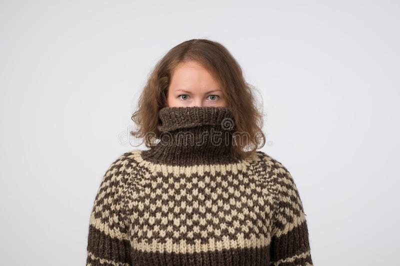Woman in warm brown sweater hiding her face. Only eyes are seen. She wants to stay anonym. stock photos