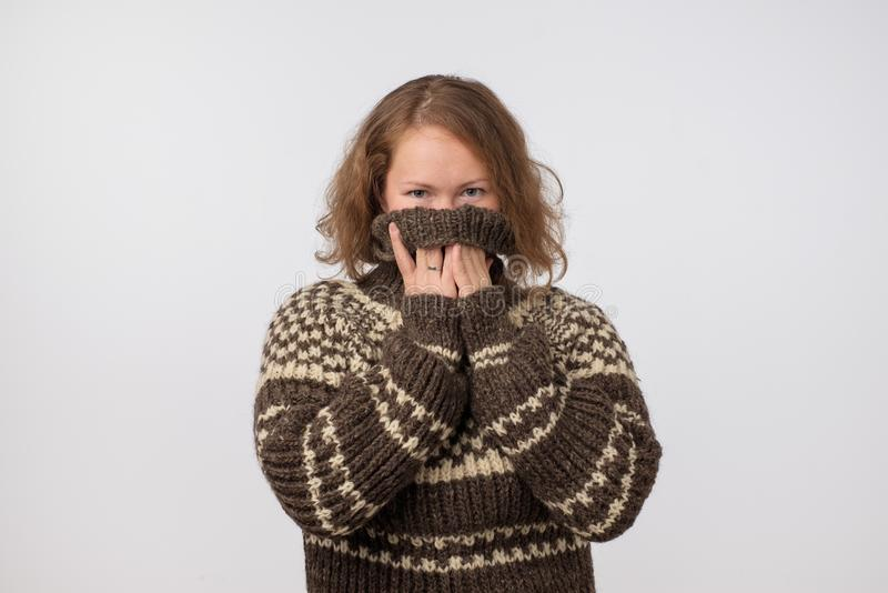 Woman in warm brown sweater hiding her face. Only eyes are seen. She wants to stay anonym. royalty free stock photography