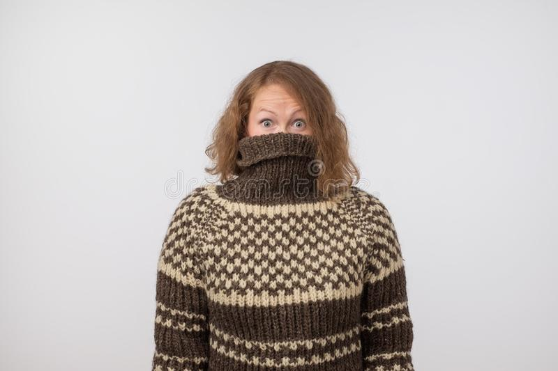 Woman in warm brown sweater hiding her face. Only eyes are seen. She wants to stay anonym. royalty free stock photo