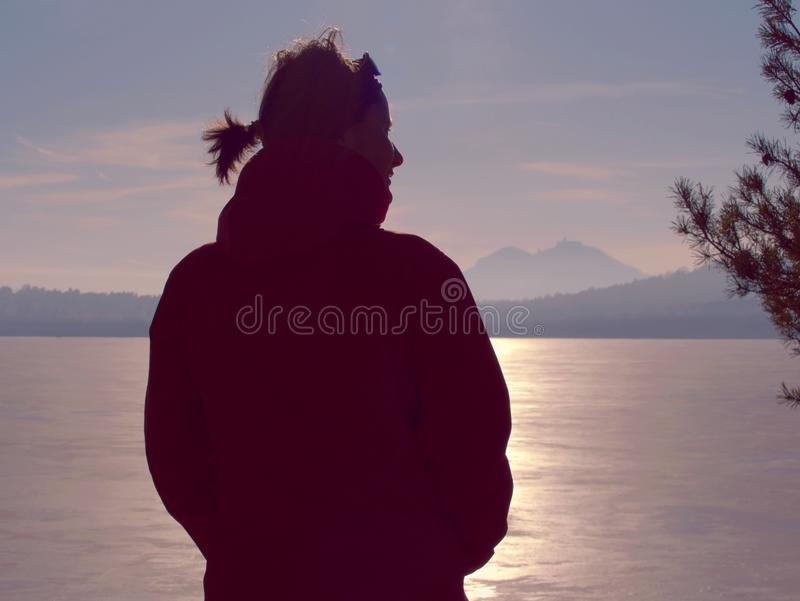 Woman in warm clothes enjoy sunbathing at frozen lake. Winter sunny day walks at lake. Strong flares in icy lake cover weather tourist sunset snow sky single royalty free stock photos