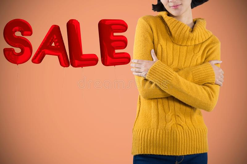Composite image of woman in warm cloths standing with arms crossed against white background royalty free stock photos
