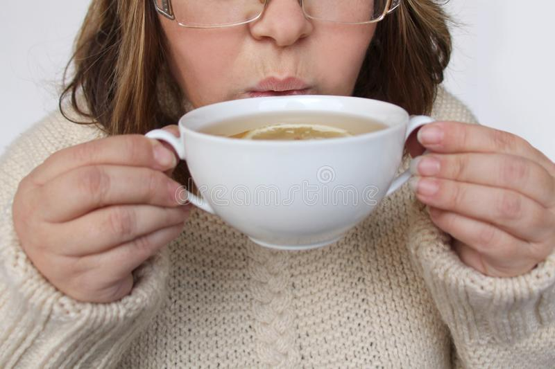 Woman in a warm knitted beige sweater holds both cups with a white cup of tea with lemon and drinks a hot drink, cozy home, close- stock photography