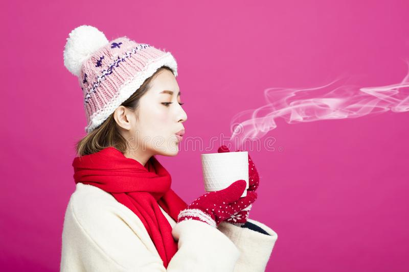 Woman in warm sweater drinking a cup of tea. Woman in warm sweater drinking a cup of hot tea royalty free stock photo